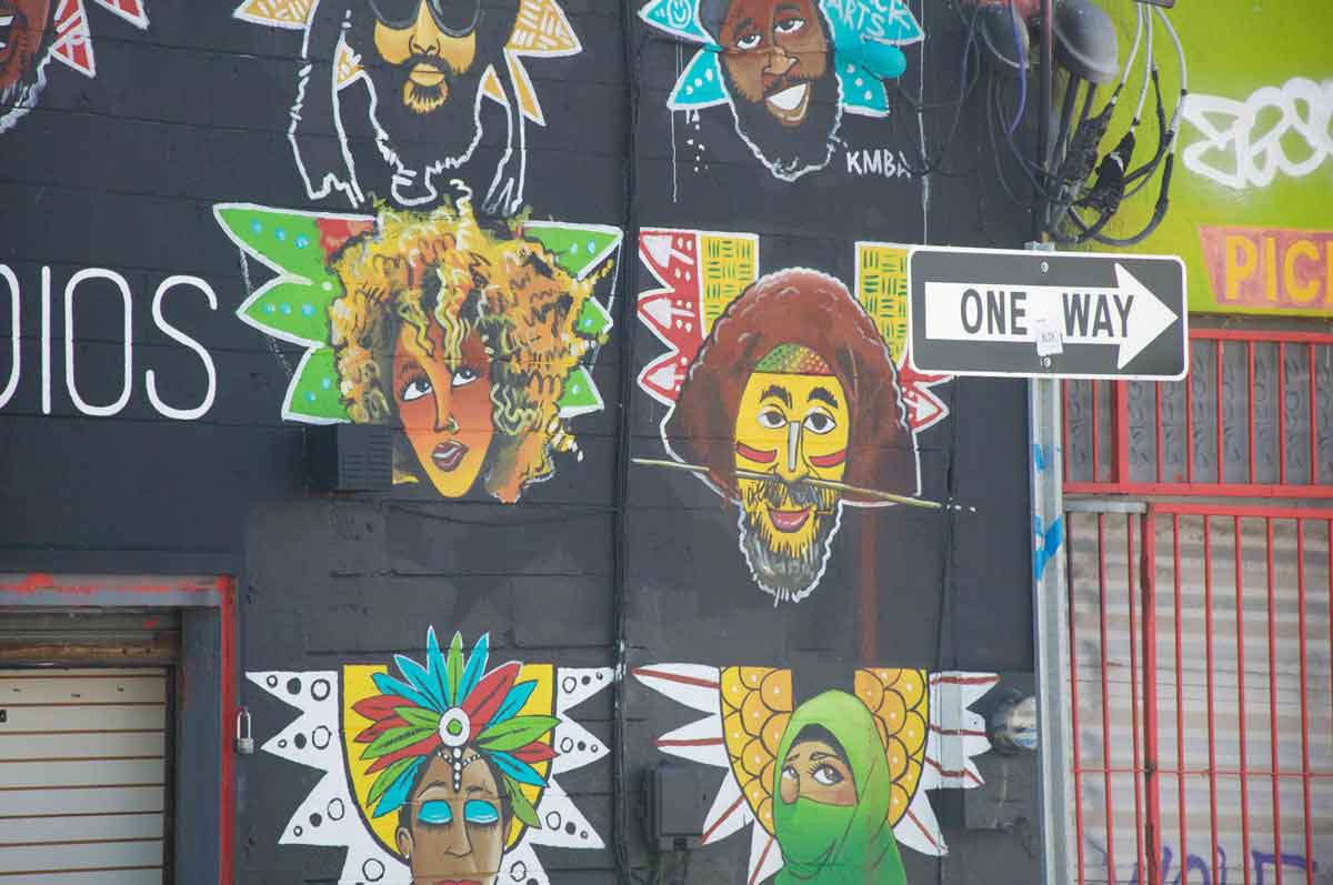 """Symbolbild für """"Kunden und Referenzen"""": ein Streetart-Graffiti an einer Hauswand. Man sieht sechs verschiedene bunt gezeichnete Personen und davon das Straßenschild """"One Way""""."""