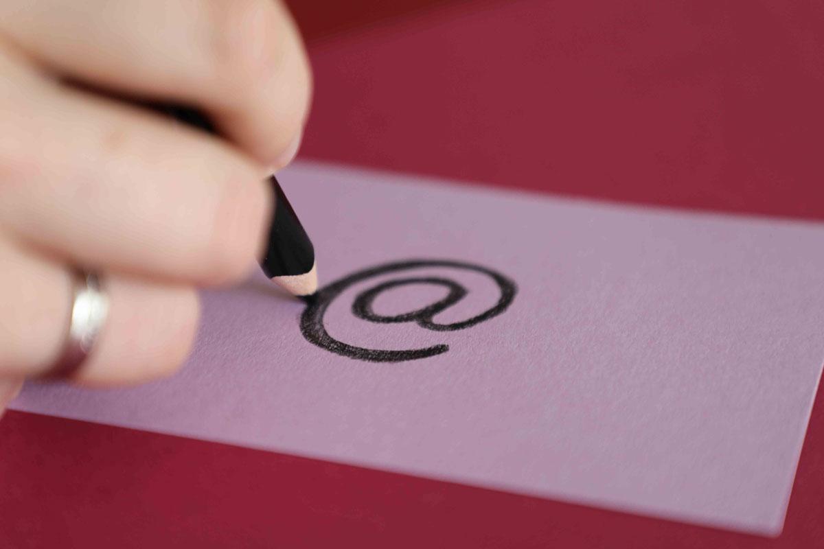 Symbolbild für Kontakt: Eine Hand malt mit einem schwarzen Buntstift ein @-Zeichen auf ein fliederfarbenes Stück Pappe.